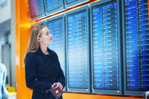 blonde women examines digital sign information in the airport