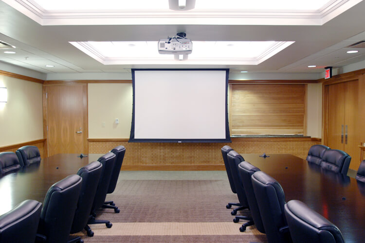 conference room with two tables and a projector screen