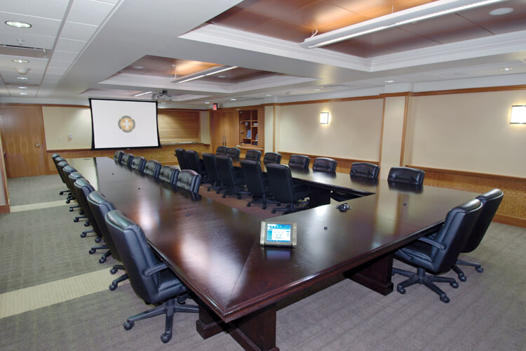 video conferencing table with chairs and dropdown screen