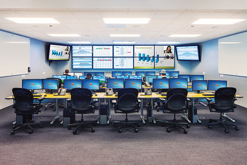 Room with many desks with dual computer monitors, digital signage displays, and a video wall
