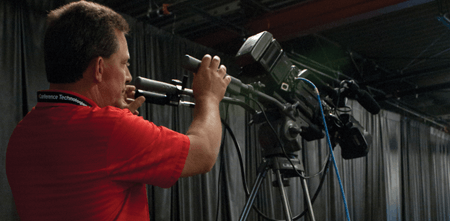man adjusts av camera for event