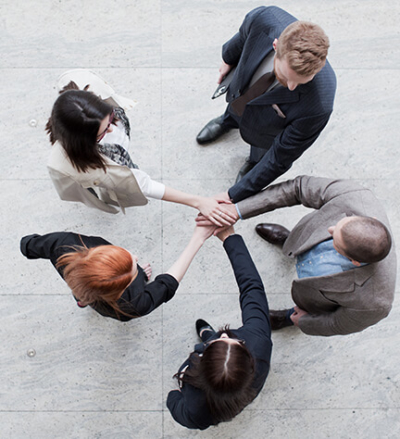 group of people standing with hands together