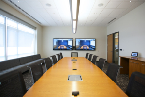video conference room, long table with chairs and video screens