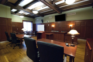 small courtroom with a mounted monitor above the judge's stand