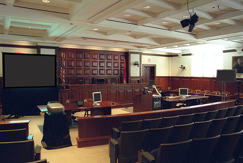 Courtroom with projector, screen and monitors on the tables