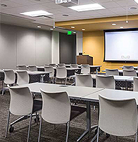 classroom with podium, retractable screen and a projector