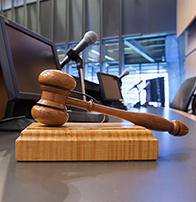 judge's gavel on desk with microphone and monitor