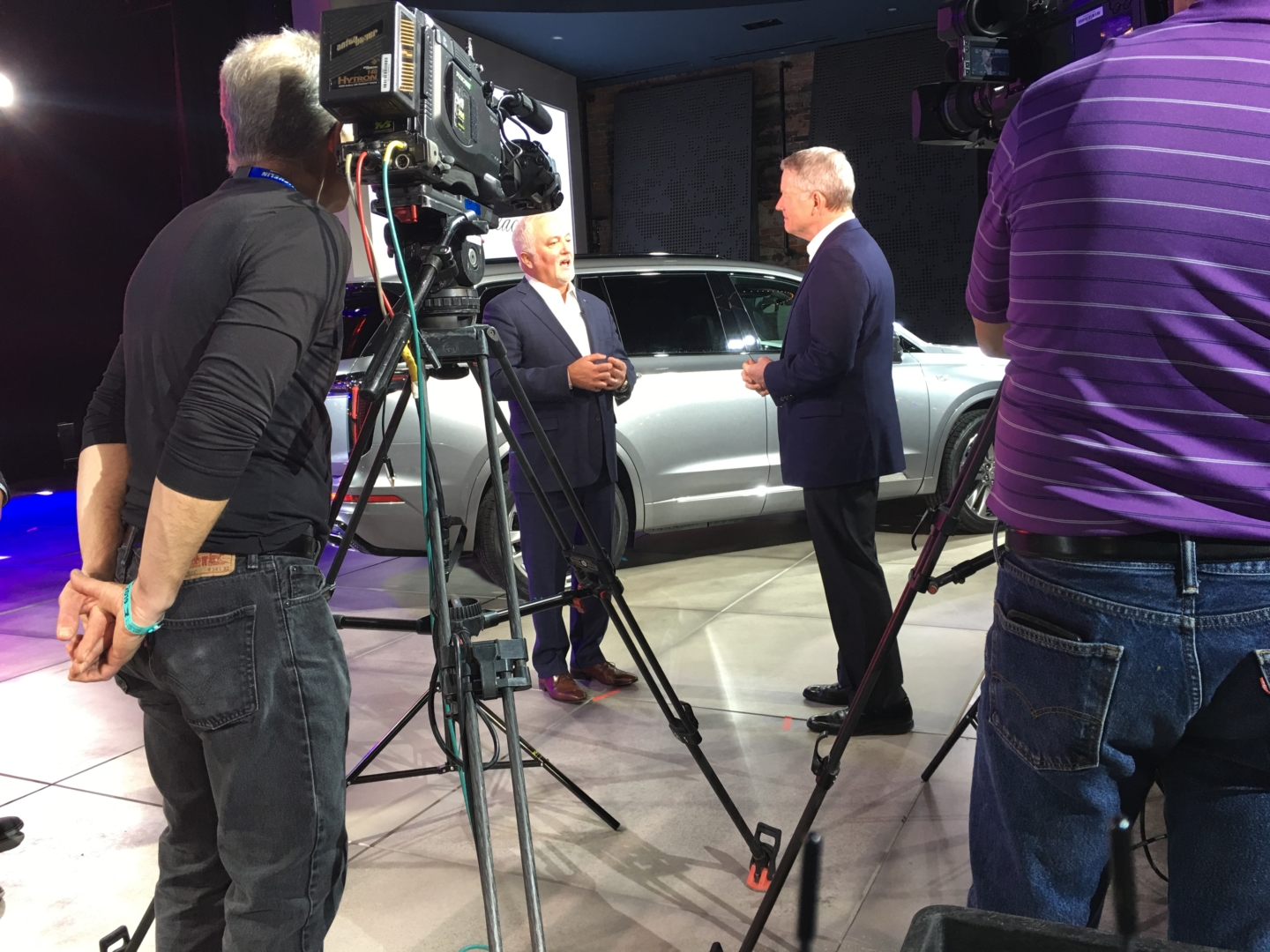 Two men are speaking in front of a camera next to vehicles on display at the 2019 Detroit Auto Show