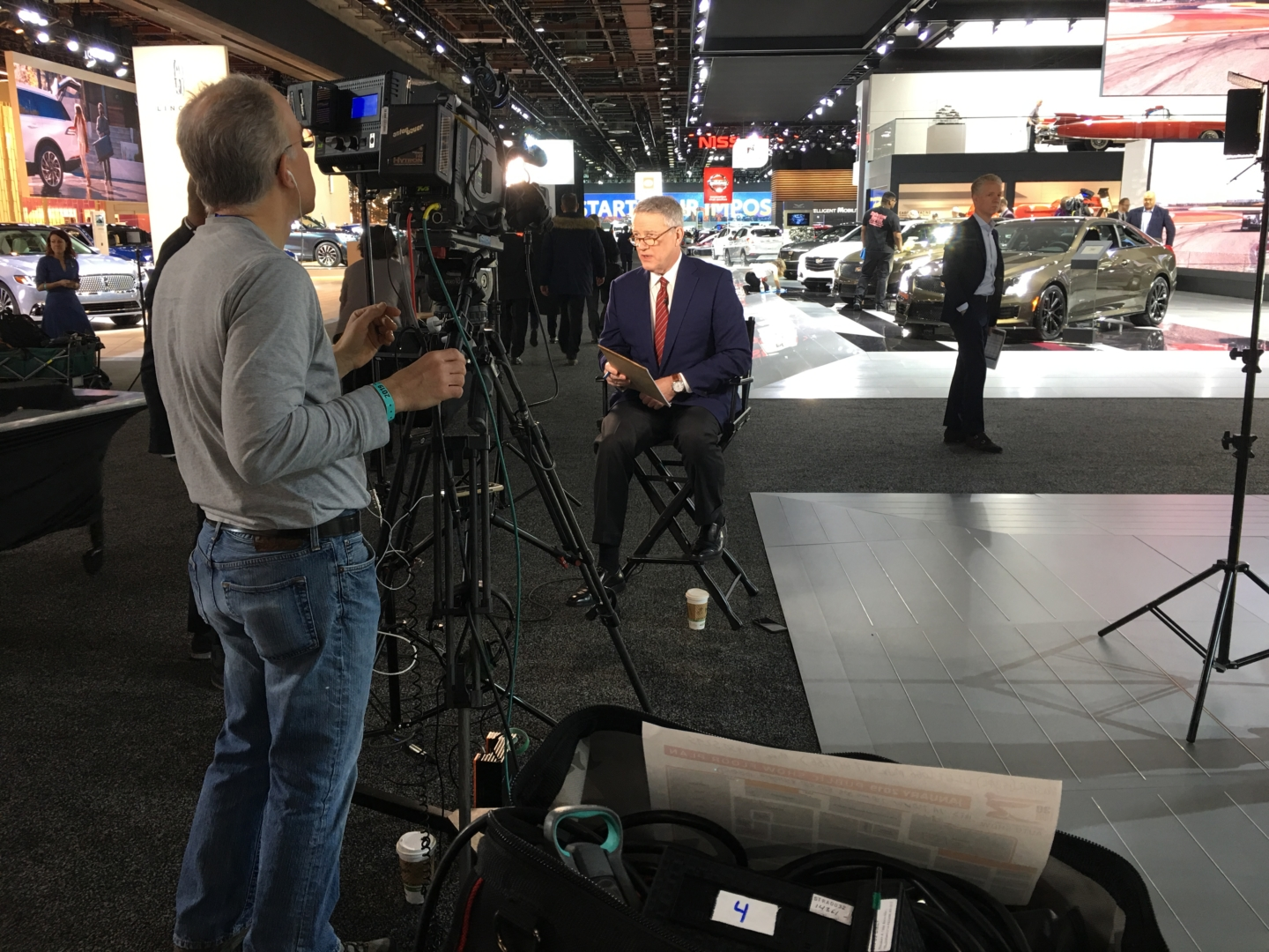 A man is speaking in front of a camera next to vehicles on display at the 2019 Detroit Auto Show