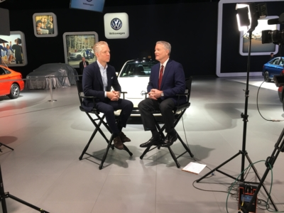 Two men are seated, speaking in front of a camera next to vehicles on display at the 2019 Detroit Auto Show