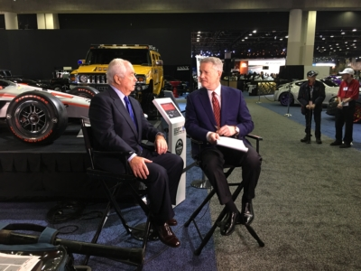 Two men are seated, speaking, next to vehicles on display at the 2019 Detroit Auto Show