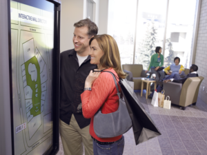 A man and a woman at a shopping mall looking at a map on an interactive smart kiosk