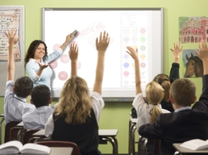 children in a classroom raise hands to answer question