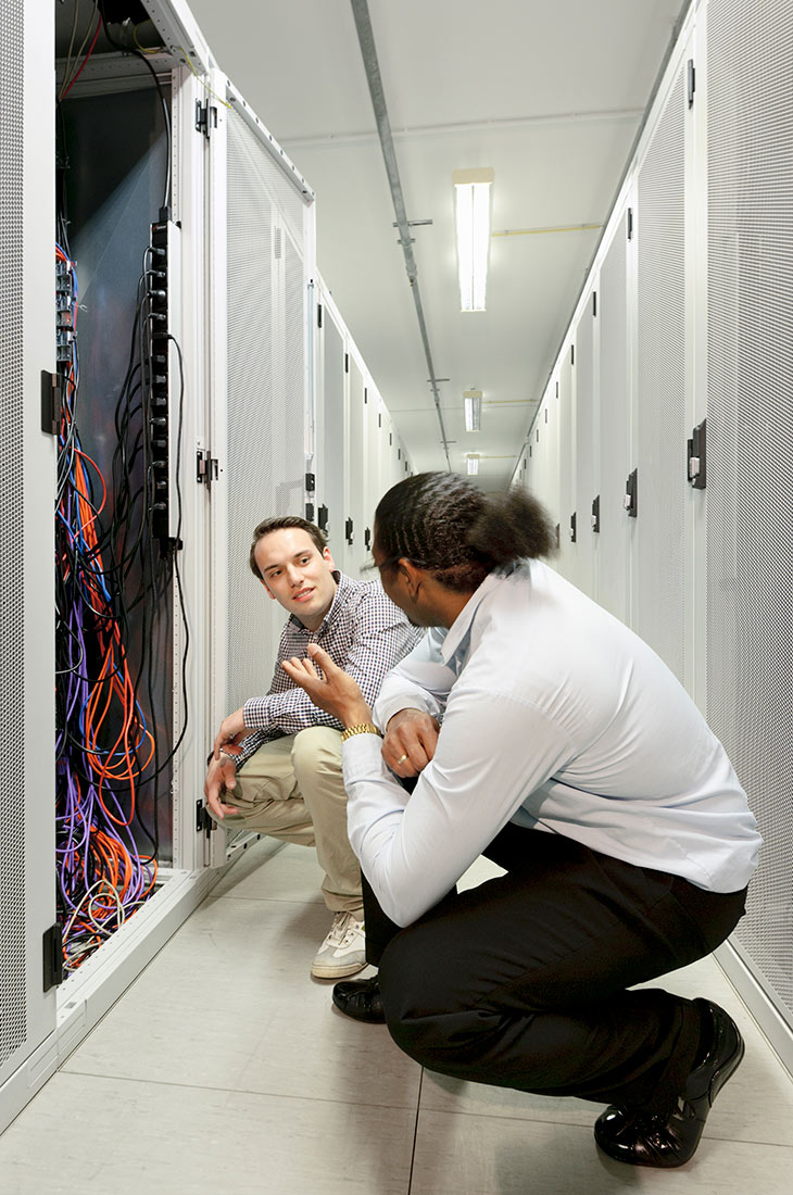 two businessmen looking over a cable network system