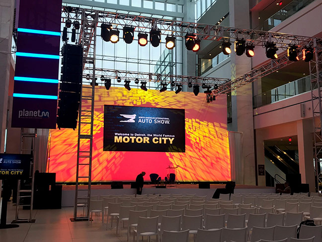 large orange backdrop, display, and lights at an auto show