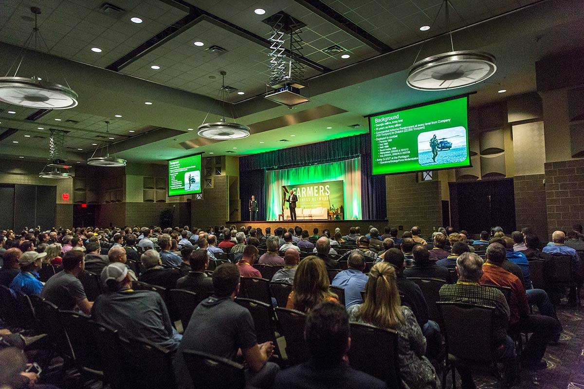 a large conference with two large projector screens and a custom backdrop and lighting