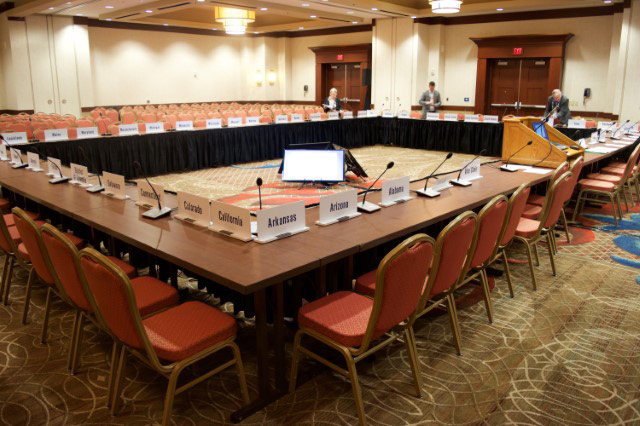 large conference table with displays in the center and microphones at each seat