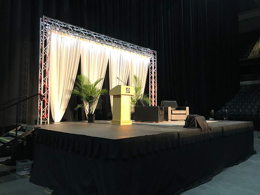 podium and chairs on an event stage with lighting and a backdrop