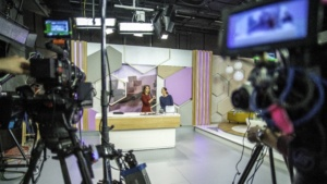 Photo of video recording equipment and stage in a broadcasting studio during the filming of a TV show.