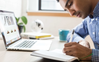 man writing notes in front of a laptop