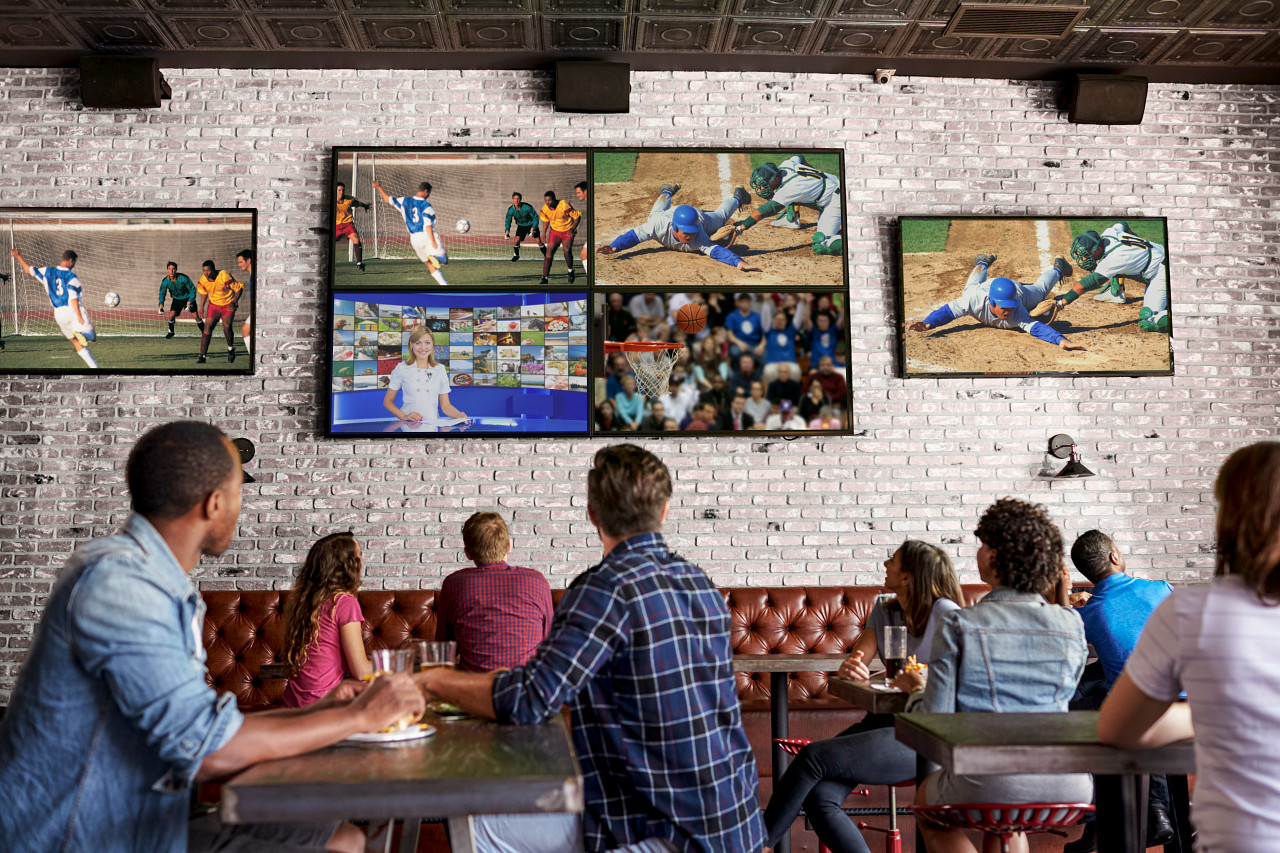 people watching many different sports on TVs at a bar