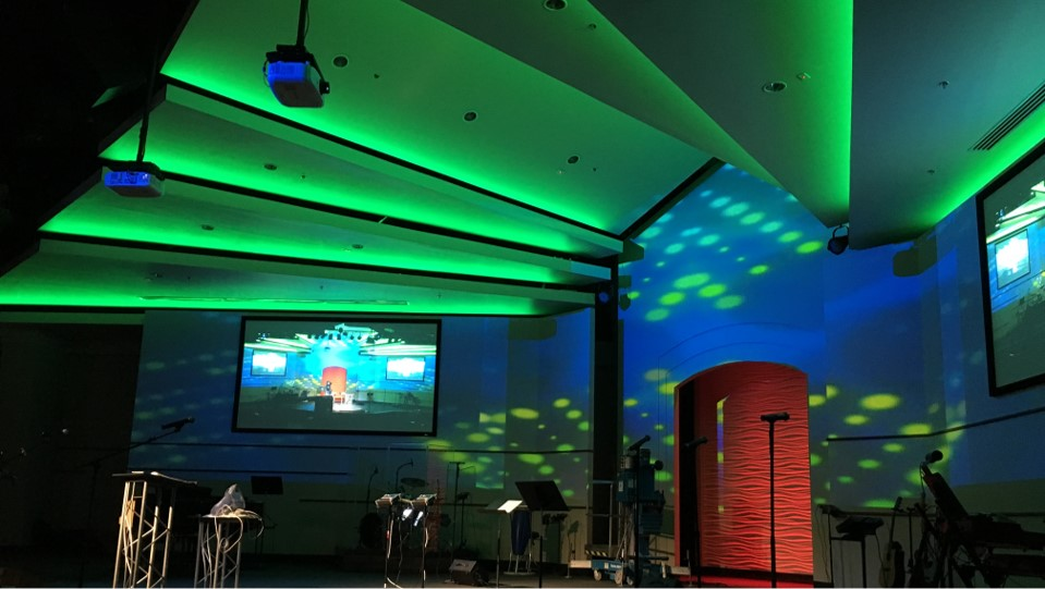 stage with custom lighting, video mapping, a large projector screens, speakers