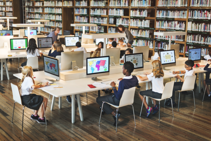 classroom technology with k12 kids on computers in a library